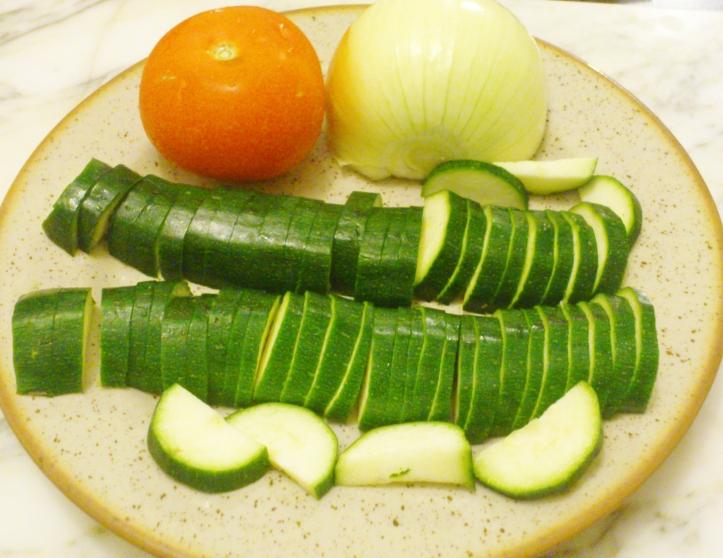 Emincez les courgettes et  les oignons et taillez les tomates en dès
