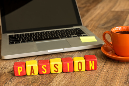 Passion written on a wooden cube in front of a laptop